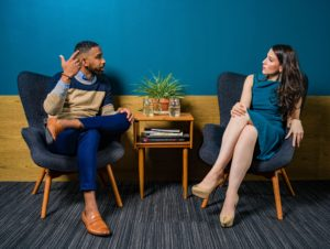 woman-wearing-teal-dress-sitting-on-chair-talking-to-man-2422280